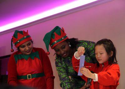 Une fille démontrent un tour de magie avec des employées d'Afrique au Féminin