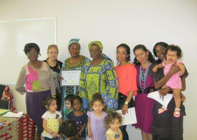 Des femmes tiennent des certificats derrière des jeunes filles