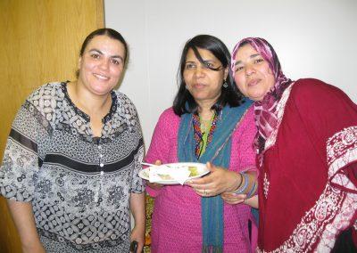 Trois femmes sourient et une tient un plat