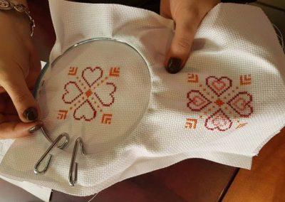 Une femme tient son projet de broderie en forme de coeur